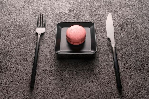 Roze makarontaart in een zwart bordje. een mooie foodfoto, een concept voor de inrichting van een coffeeshop of bar, restaurant. donkere grunge achtergrond, tabel instelling.