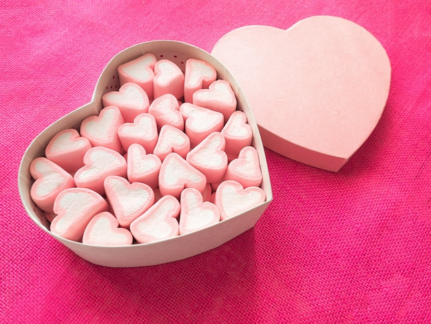 Roze marshmallow in een geschenkdoos in vorm van hart op roze doek