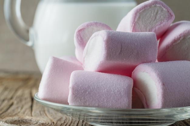 Roze marshmallow met melk op houten tafel