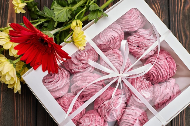 Roze marshmallow, verpakt in een doos met een lint en bloemen, voor een cadeau, op een houten bord