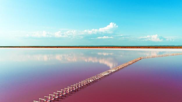 Roze meer en zandstrand met een zee baai onder een blauwe hemel met wolken