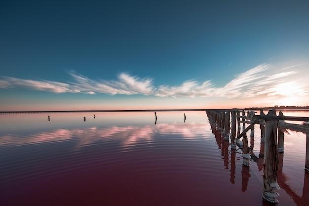 Roze meer en zandstrand met een zee-baai onder een blauwe hemel met wolken