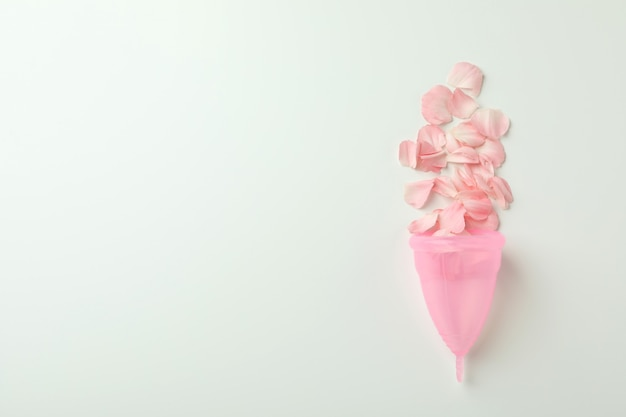 Roze menstruatiecup met bloemblaadjes op wit