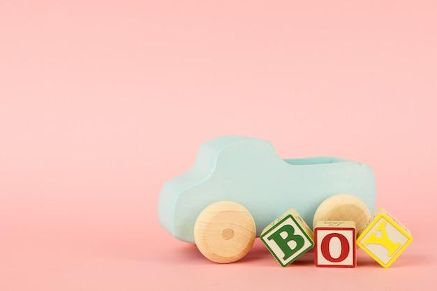 Roze met gekleurde kubussen met letters jongen en speelgoedauto