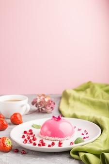 Roze mousse cake met aardbei en een kopje koffie