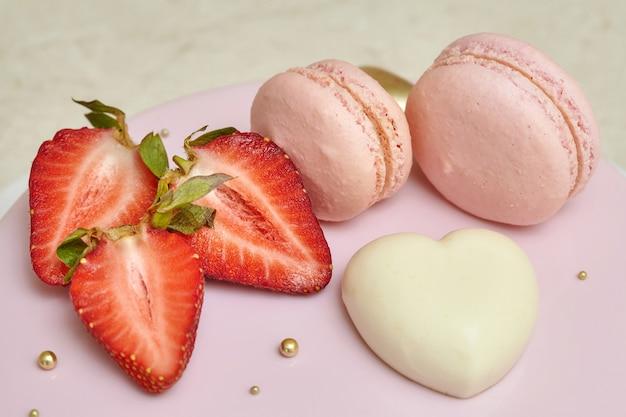 Roze mousse cake mirror glaze, versierd met macarons en aardbei