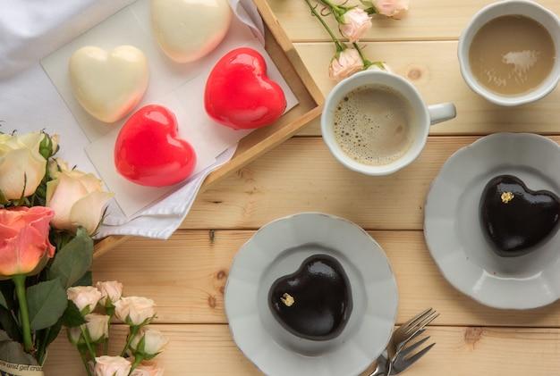 Roze mousse cakes in de vorm van een hart versierd met mini harten op een houten rustieke achtergrond. hartvormige cakes voor valentijnsdag of moederdag. bovenaanzicht plat leggen