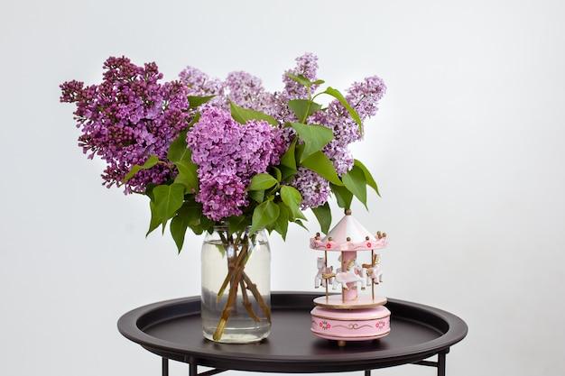 Roze muzikale carrousel en boeket van prachtige lila lentebloemen in vaas op vintage salontafel. vintage muzikale carrousel speelgoed