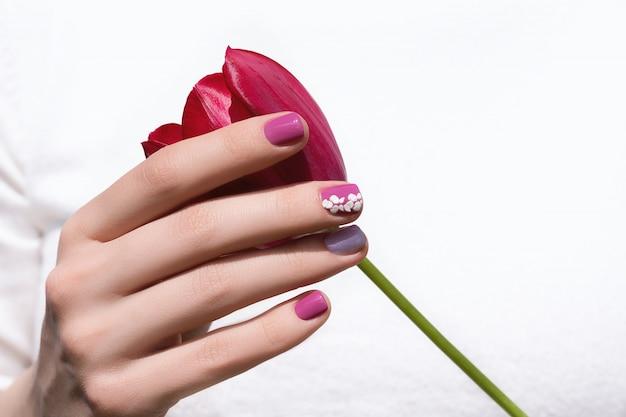 Roze nagelontwerp. vrouwelijke hand met roze de tulpenbloem van de manicureholding