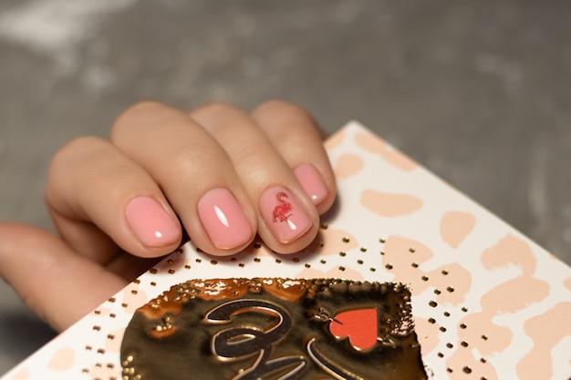 Roze nagelontwerp. vrouwelijke hand met roze manicure.