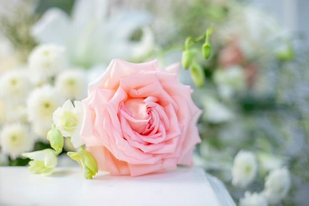 Roze nam bij huwelijksceremonie toe op onduidelijk beeldachtergrond. ondiepe diepte van het veld.