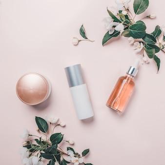 Roze natuurlijke cosmetica: olie, serum, crème, masker op achtergrond met bloemen. plat leggen, minimalisme.