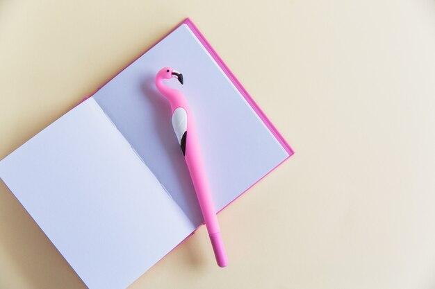 Roze notitieblok voor notities, grappige flamingo pen op roze pastel achtergrond. plat leggen. bovenaanzicht kopieer ruimte