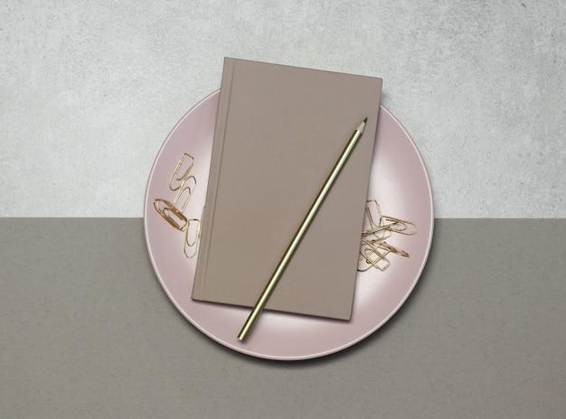 Roze notities met gouden potlood en clips op grijs