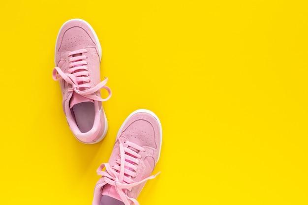 Roze nubuck sneakers geïsoleerd op een gele achtergrond, seizoensgebonden schoenen om te wandelen en sporten, bovenaanzicht