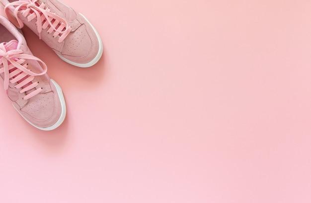 Roze nubuck sneakers geïsoleerd op een roze achtergrond, seizoensgebonden schoenen om te wandelen en sporten, bovenaanzicht