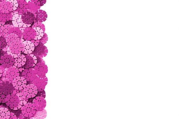 Roze ontwerper achtergrond. roze details in de vorm van sneeuwvlokken van de kinderontwerper. kunststof schijven voor de ontwikkeling.