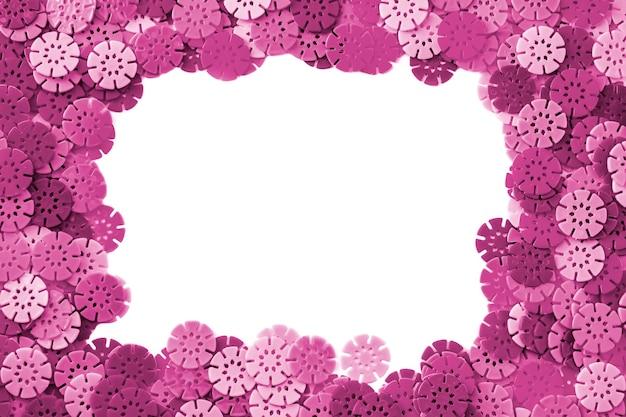 Roze ontwerper achtergrond. roze details in de vorm van sneeuwvlokken van de kinderontwerper op witte achtergrond. plastic schijven voor de ontwikkeling van de fijne motoriek van de vingers.