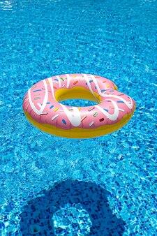 Roze opblaasbare donut donut in zwembad