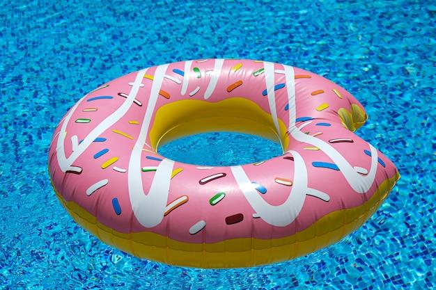 Roze opblaasbare donut in het zwembad