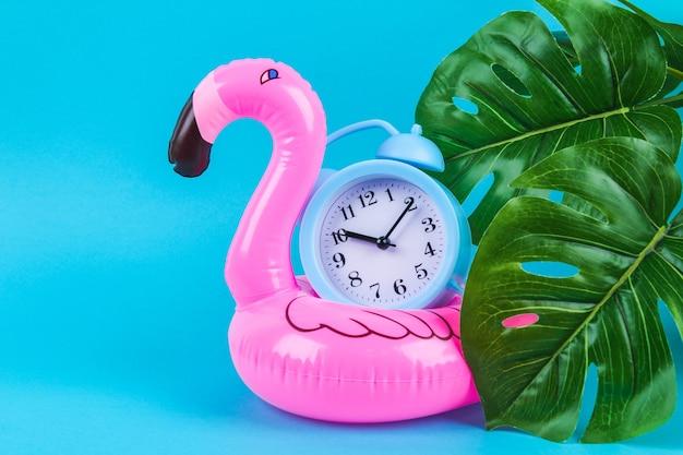 Roze opblaasbare flamingo op blauw met monsterabladeren en klok.