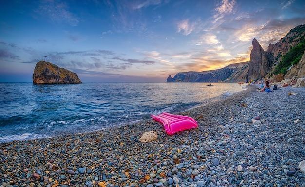 Roze opblaasbare matras op het kiezelstrand bij zonsondergang. rotsachtig uitzicht op zee met een opblaasbaar matras.