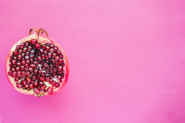 Roze oppervlak met granaatappel en lege ruimte