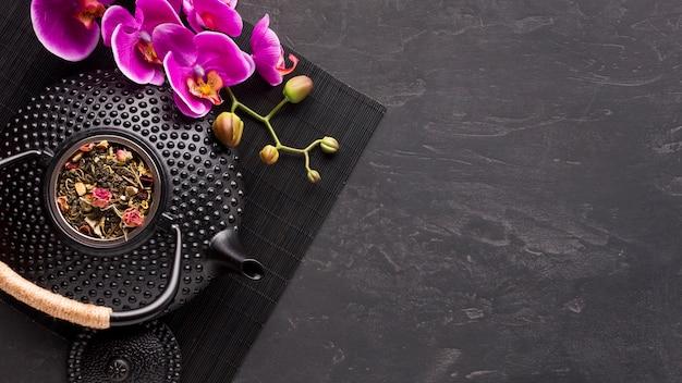 Roze orchideebloem en droog theekruid met textuur ceramische theepot op zwarte placemat