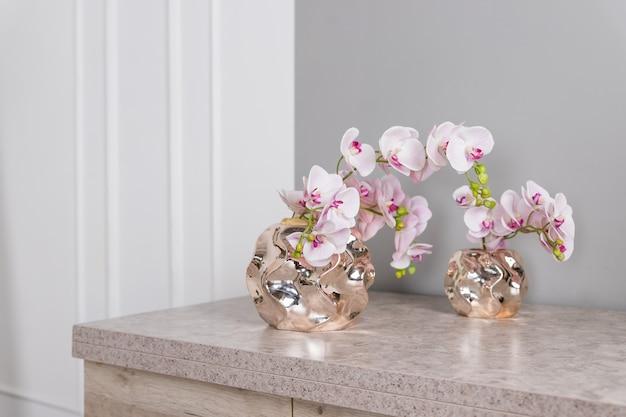 Roze orchideebloemen in gouden vaas op een marmeren tafel. huisdecoratie concept.