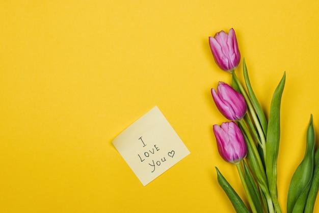 Roze, paarse tulpen en een plakbriefje met de tekst i love you op een gele muur