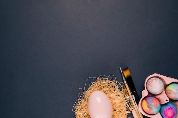 Roze paasei in nest; penselen en eierdoos op de hoek van de zwarte achtergrond