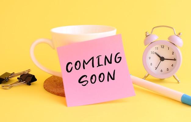 Roze papier met de tekst coming soon op een witte kop. klok, pen op een gele tafel.