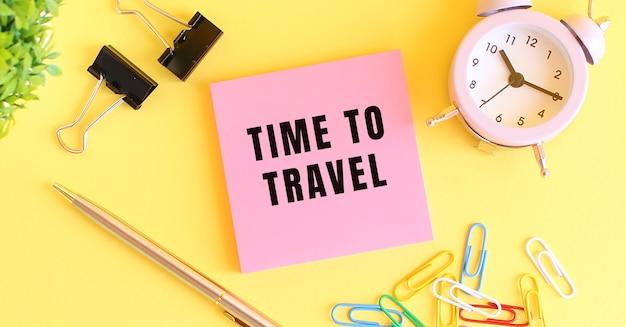 Roze papier met de tekst time to travel. klok, pen op een gele achtergrond. concept ontwerp.