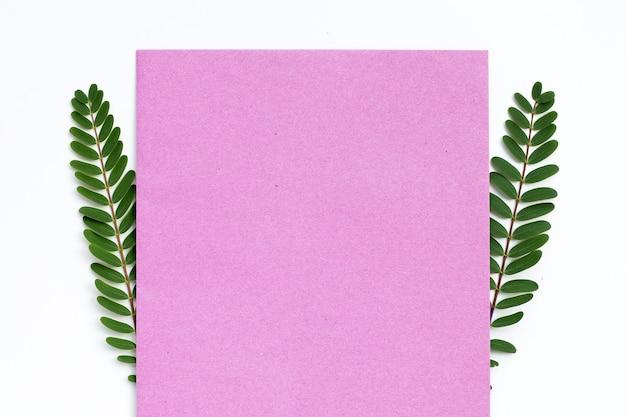 Roze papier met groene bladeren op een witte achtergrond.