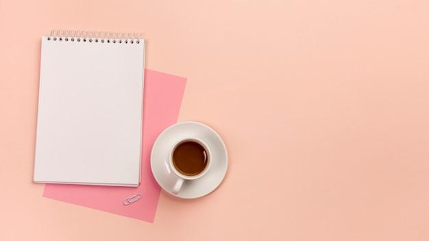 Roze papier, spiraal kladblok en koffiekopje op perzik gekleurde achtergrond