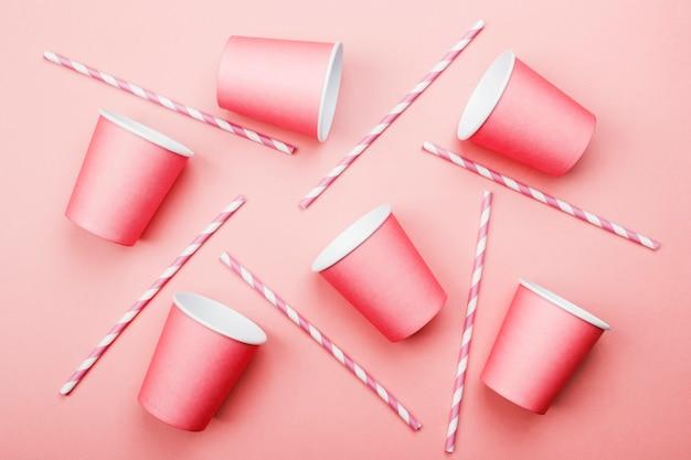 Roze papieren bekers en roze-witte stro op roze