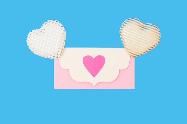 Roze papieren enveloppen en hartvormige decoratie op blauwe achtergrond in valentijnsdag stijl