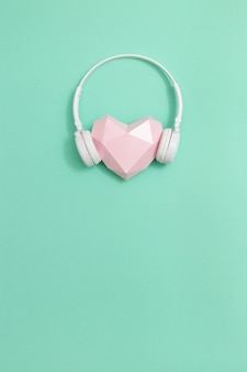 Roze papieren hart in witte koptelefoon