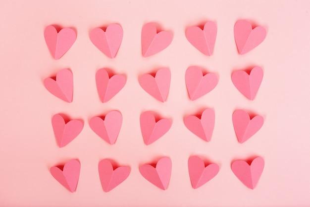 Roze papieren harten gerangschikt in rijen op roze achtergrond