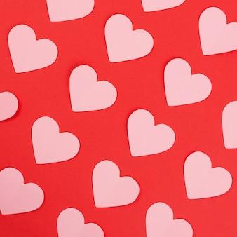 Roze papieren harten op rode achtergrond