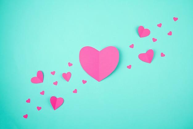 Roze papieren harten over de turkooizen achtergrond. sainte valentine, moederdag, verjaardagswenskaarten, uitnodiging, vieringsconcept