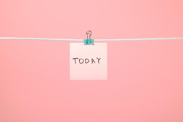 Roze papieren notitie opknoping op de string met tekst vandaag