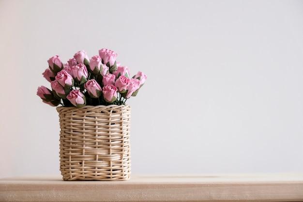 Roze papieren rozen in de mand op de tafel met kopie ruimte minimale stijl