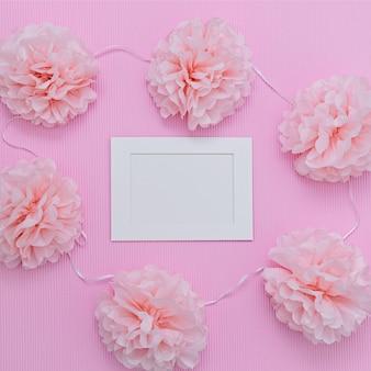 Roze papieren snijbloemen en wit frame met witte blanco