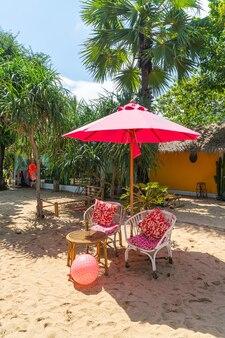 Roze paraplu en stoel op tropisch strand