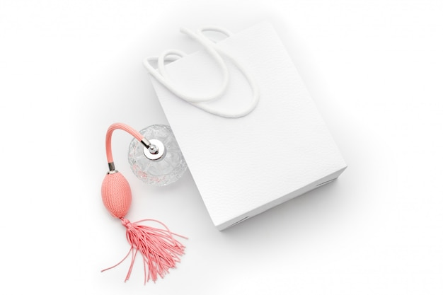 Roze parfumfles met witte papieren boodschappentas. parfumerie, cosmetica, geurcollectie. thema voor verkoop, mode, winkelen en adverteren.