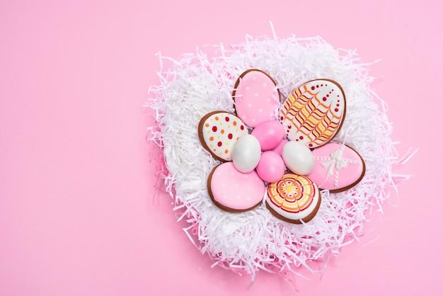 Roze pastel achtergrond met paaseieren en smakelijke koekjes