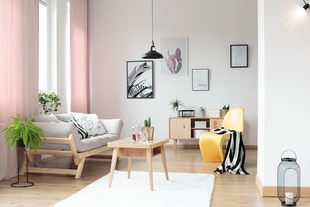 Roze pastelgordijnen in woonkamer en gele designstoel