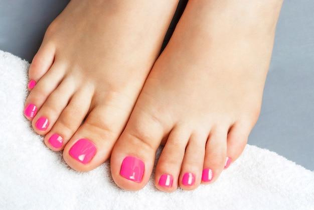 Roze pedicureclose-up, dat op grijs wordt geïsoleerd