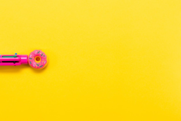 Roze pen in de vorm van een donut geïsoleerd op een gele achtergrond veelkleurige pen terug naar school